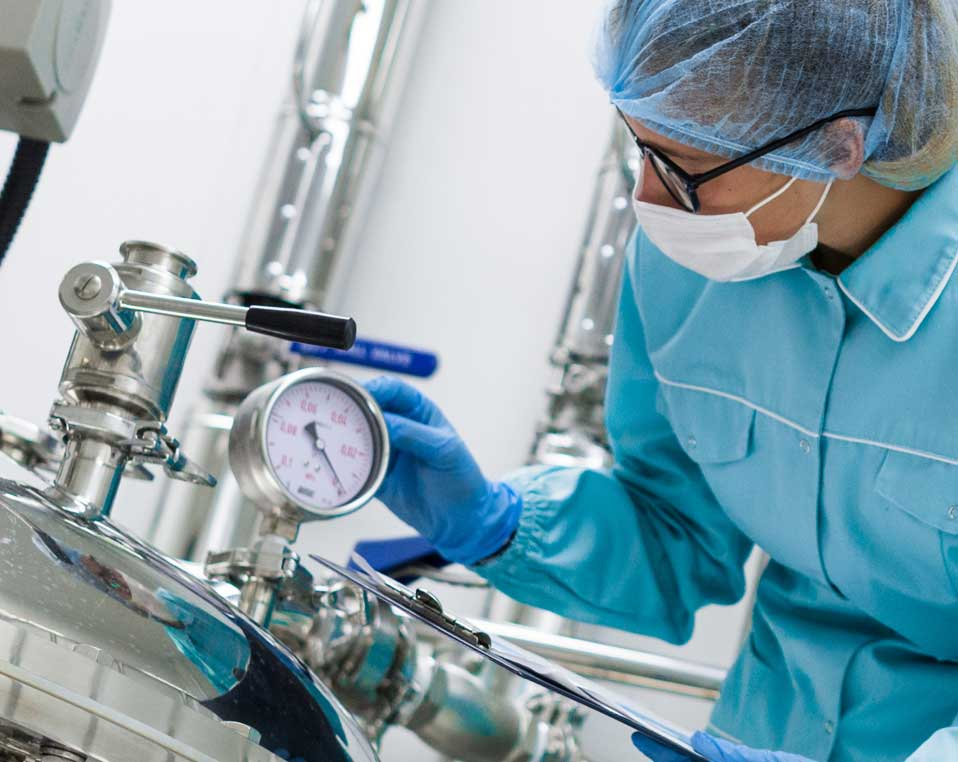 Lab worker inspecting gauge on equipment